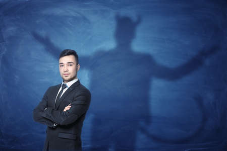 conscience: A businessman standing with his hands across and his shadow on a blue empty blackboard behind him with hands overspread, horns and a tail like a devil has. Self-confident behavior. Hidden feelings. Inner anger.
