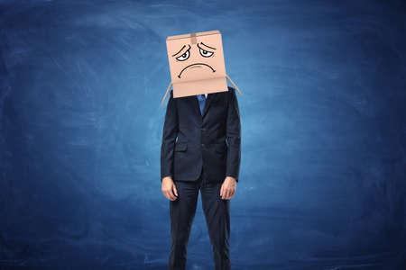 ビジネスマンが身に着けている青い黒板近く彼の頭に描かれた悲しい顔と段ボール箱。匿名の人物。梱包と梱包します。中小企業の問題。