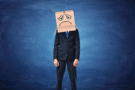 Businessman wearing cardboard box with drawn sad face on his head near the blue blackboard. Anonymous person. Packing and crating. Issues of small business.