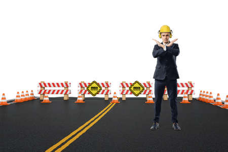 roadwork: Businessman in yellow helmet and headphones standing on the road under construction with his arms crossed in stop gesture. Road repair service. Under construction. Construction site. Stock Photo