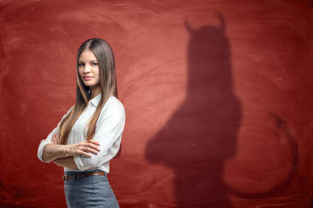 impostor: Young businesswoman is casting shadow of devil on rusty orange wall behind her. Unfair competition. Aggressive marketing strategies. Hidden motives. Stock Photo