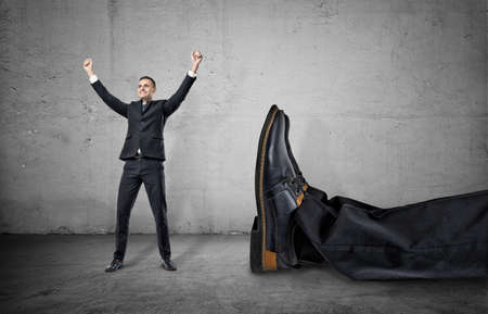 A small businessman standing with his arms up and smiling happily near a giant leg in trousers and shoe lying near him, on the concrete gray background. Winning contest. Best in field. David and Goliath. Small company wins big one.