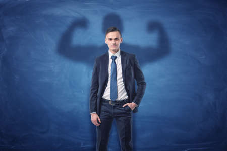 shadow man: Businessman is casting shadow of big strong muscular man showing his biceps. on blue chalkboard background. Inner strength. Leadership qualities. Business development.