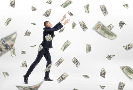 money flying: Una gran cantidad de dinero en efectivo de vuelo y un hombre de negocios que se enganche en el fondo blanco. la aspiración éxito. negocio próspero. Ganar dinero mucho og.
