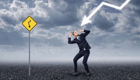 rocky road: Businessman standing on a rocky ground frightened by a lightning, near yellow road sign with the same arrow painted on it. Business crisis. Temporary difficulties. Emotional pressure.