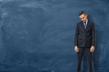 A sad businessman in a suit standing with bowed head and his arms down near the blue chalkboard. Face serious challenges. Business difficulties. Get into trouble.