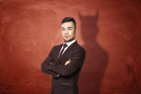 arms folded: Businessman in suit standing with his arms folded, he is casting shadow of the devil on the rusty orange wall behind him. Unfair competition. Aggressive marketing strategies. Hidden motives.