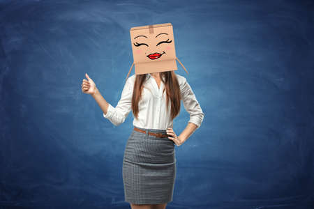 smiley pouce: Young beautiful woman showing her thumb up and wearing cardboard box with drawn smiley face with red full lips. Anonymous person. Support and approval. Good idea. Success in business. Banque d'images
