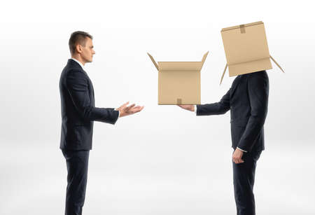 fitting in: Businessman with a cardboard box on his head passed another box to another man, on white background. Business world. Communication at work. Fitting in.