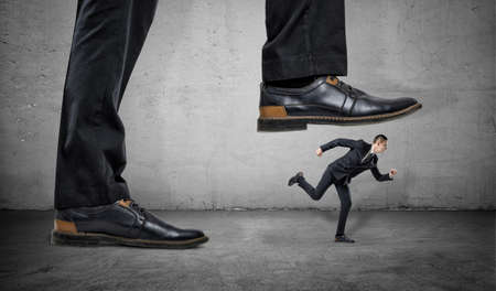 suppression: A businessman is running away from a big foot on a gray concrete background. Suppression of competitors. Big business.