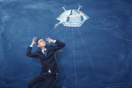 Businessman frightened by flying saucer painted on blue blackboard behind him 免版税图像