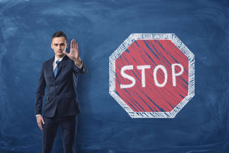 him: Businessman standing with his arm forward and traffic-sign Stop painted on blackboard behind him