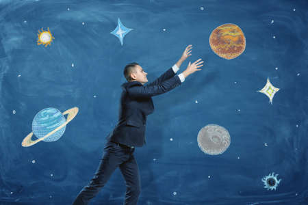 grasp: Businessman on blue chalkboard background trying to grasp a drawn planet among many others.