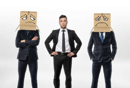 similarity: One businessman standing between two other men wearing carton boxes with drawn sad faces on them.
