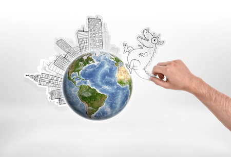 Mans hand holding cartoon funny monster going to attack city put around the globe on