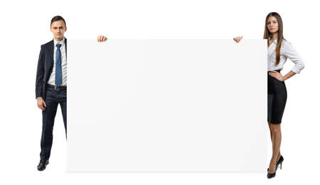 Businessman and businesswoman are holding both sides of a blank banner isolated on white background