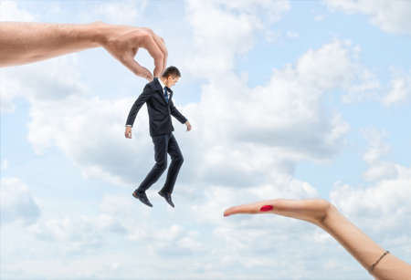conquering adversity: Mans hand is carrying a little businessman to a womans hand on the backgroung of blue sky Stock Photo