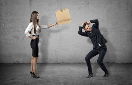 cowering: Businesswoman on concrete background holding a carton box to a cowering man.
