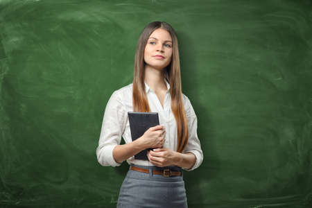 dayplanner: Young businesswoman holding her dayplanner and thinking on the green chalkboard background Stock Photo