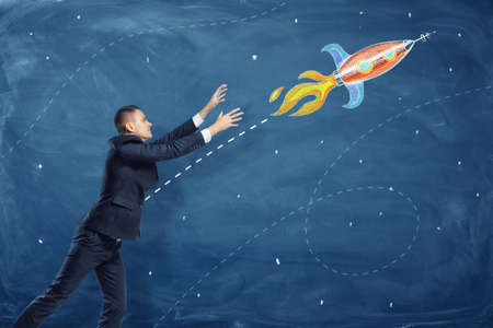 A businessman pulling up his hands to a flying through the sky rocket painted on a blackboard
