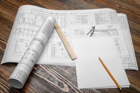 A set of open and rolled up blueprints on wooden table background with a pencil, a ruler and compasses lying beside. Standard-Bild