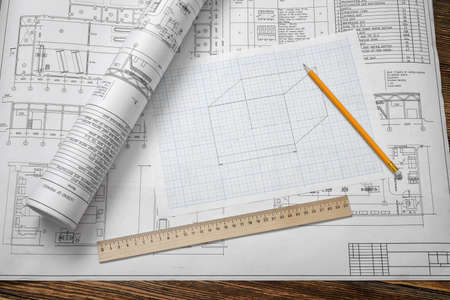 A set of open and rolled up blueprints on wooden table background with a pencil and a ruler lying beside.
