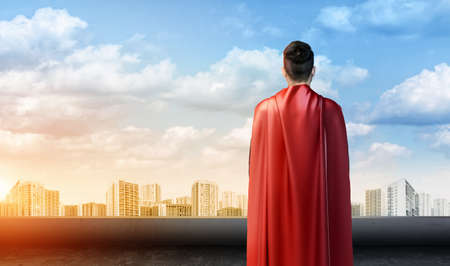 A businessman in superman cape standing turned back on the sky background with cityscape below.