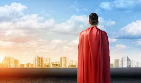 Ein Geschäftsmann in Übermensch Umhang stehend drehte auf dem Himmel Hintergrund mit Stadtbild zurück unten. Standard-Bild