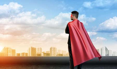 スーパー ヒーロー岬に立ってのビジネスマンは、都市景観の下で空の背景に引き返した。 写真素材