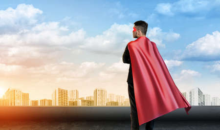 A businessman in super hero cape standing turned back on the sky background with cityscape below.