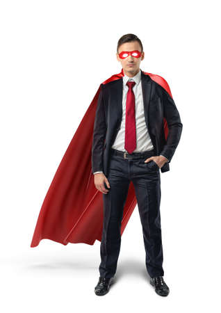 A businessman in a formal suit, a red flowing cape and a red eye mask with one hand in his pocket in front view. Stock Photo