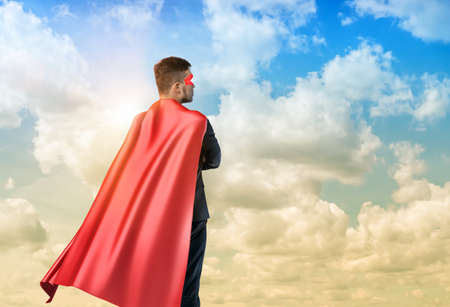 A businessman in superman cape standing turned back on the sky background