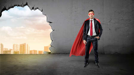 A businessman in a hero red cape with a hand in his pocket on concrete background with a hole to the city view. Stock Photo