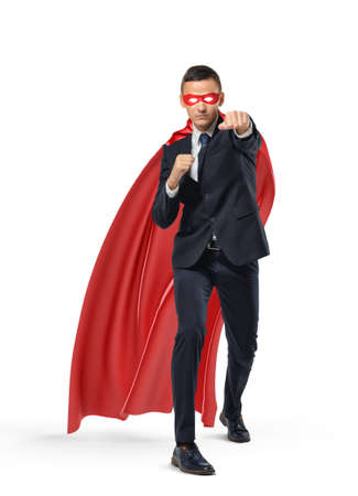 A businessman in a superman red cape and a mask standing in punch position on white background. Stock Photo