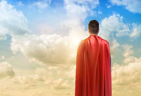 A businessman in super hero cape standing turned back on the sky background