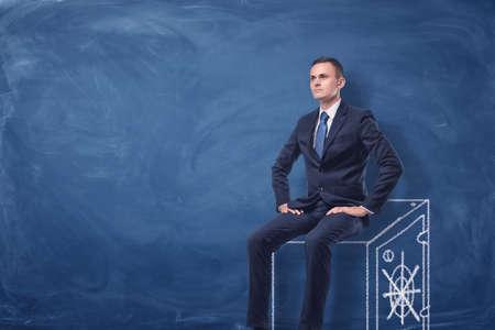 businessman on blue chalkboard background sitting on a strongbox