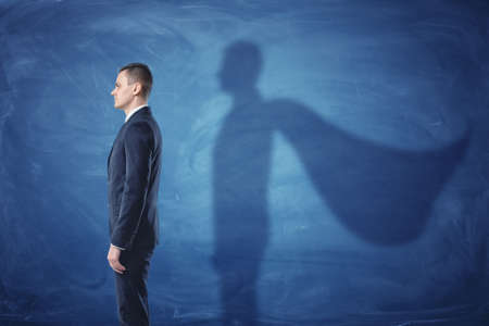 Businessman is standing in profile casting a shadow of the cape on blue chalkboard background