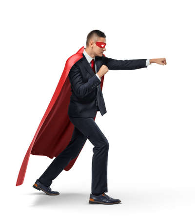 A businessman in a superhero red cape and a mask standing in side view in punch position on white background.
