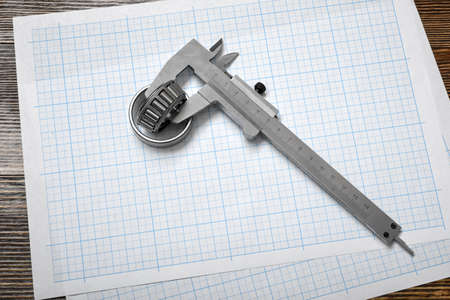 architect tools: A large vernier scale lying on cross section paper with bearings on wooden background.