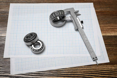 draftsman: A large vernier scale lying on cross section paper with three bearings around it on wooden background.