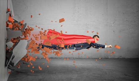 Een superheldzakenman in een kaap die net door de muur vliegen die puin achter hem verlaten.