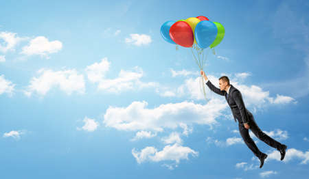 resourceful: A businessman holding a batch of colorful balloons that let him fly through the clouds. Stock Photo