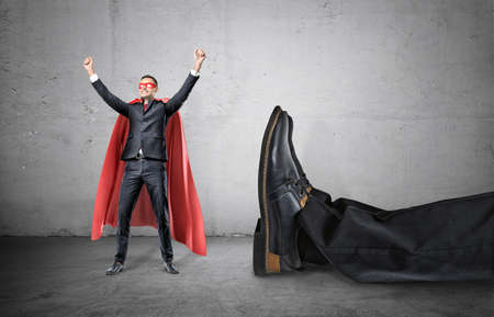 A smiling businessman in a superhero red cape with hands raised in success motion standing beside a giant human foot.