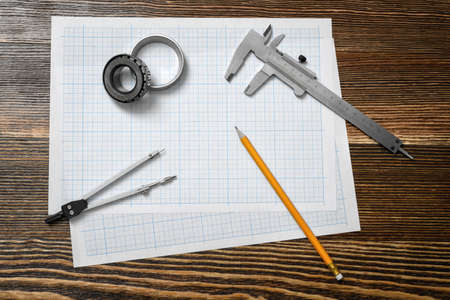 trammel: A vernier caliper holding a bearing, a pencil and a pair of compasses lying over drafting paper on wood background.