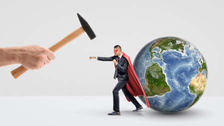 A businessman in a red superhero cape protecting a small globe behind him and punching a giant hand holding a hammer.