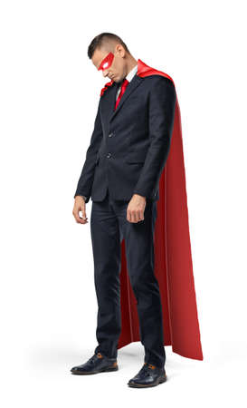 tired businessman: A sad businessman in a superhero red cape standing with his shoulders slumped and looking down.