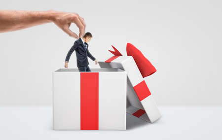 trapped: A large male hand getting a tiny businessman out from a white gift box with a red bow on white background. Stock Photo