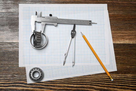architect drawing: A vernier caliper holding a bearing, a pencil and a pair of compasses lying over drafting paper on wood background.