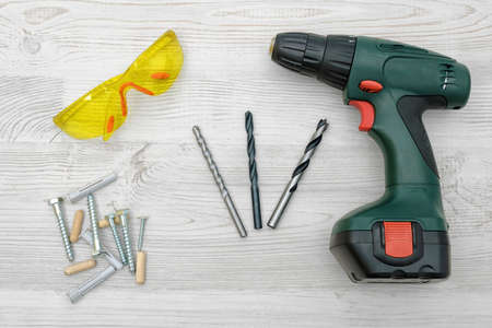 industrial machinery: A cordless drill set on a wooden table background with a set of bits in the box and yellow protective glasses around.