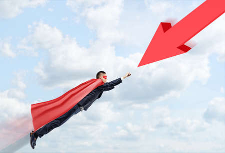 A businessman in a red cape and a mask flying through the clouds towards a huge red arrow. Problem solving. Business development. Goals and achievement.